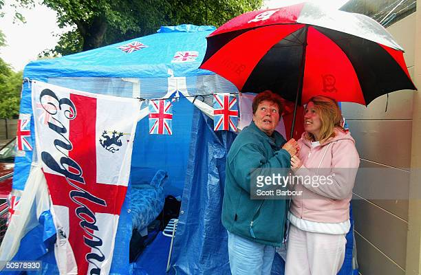 Spectators take cover from the rain as queues start to form the day before the event at the Wimbledon Lawn Tennis Championship on June 20 2004 at the...