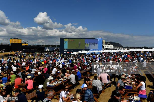 Spectators take lunch and watch the action on a big screen during round one of the 147th Open Championship at Carnoustie Golf Club on July 19 2018 in...