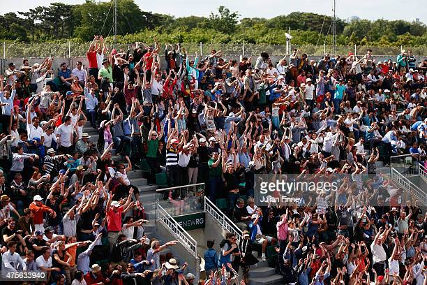 Spectators take part in a Mexican wave during the Men's quarter final match between JoWilfried Tsonga of France and Kei Nishikori of Japan on day of...