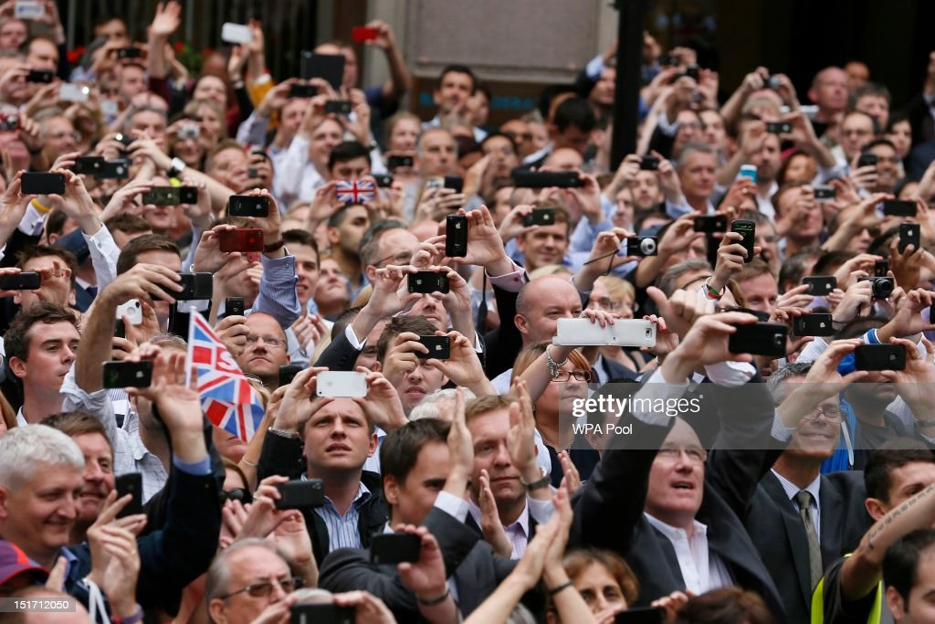Spectators take photographs during the London 2012 Victory Parade for Team GB and Paralympic GB athletes on September 10, 2012 in London, England.