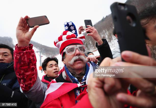 Spectators take photographs of the North Korean cheerleaders as they sing prior to the Alpine Skiing Ladies' Slalom on day five of the PyeongChang...