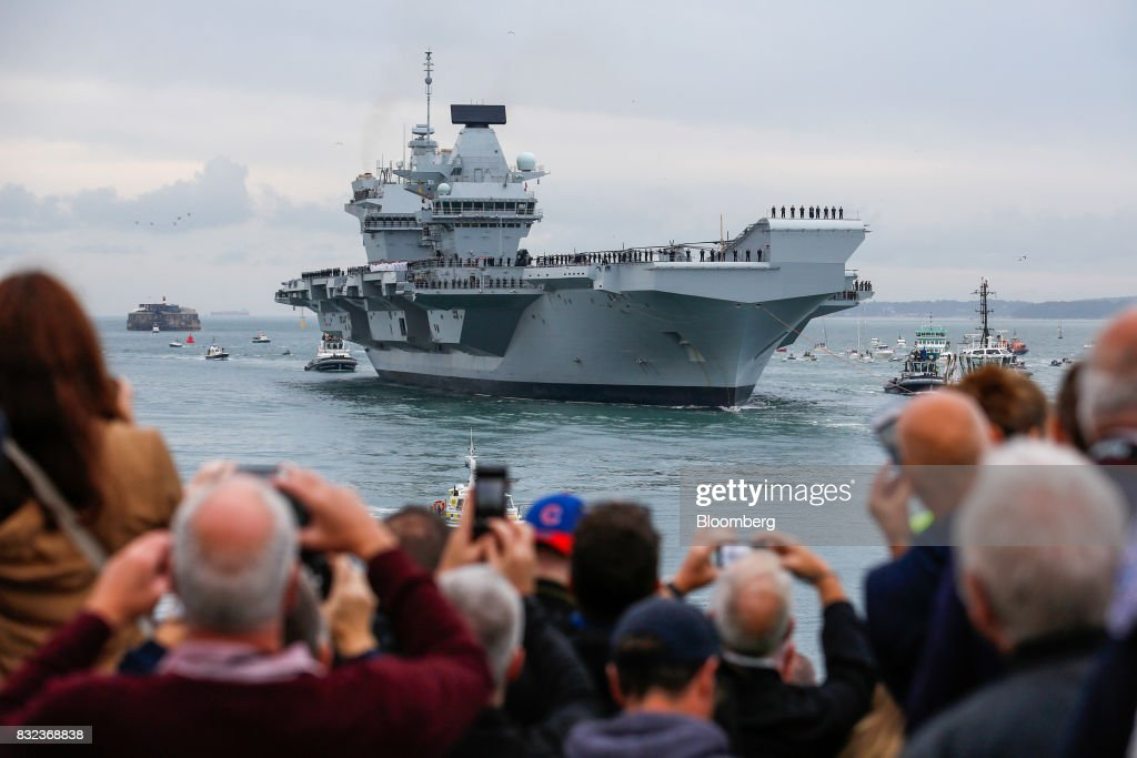 Spectators take photos as the U.K.'s Royal Navy new aircraft carrier, HMS Queen Elizabeth arrives at its home port in Portsmouth, U.K., on Wednesday, Aug. 16, 2017. The largely French-designed ship will carry 40 aircraft and about 700 crew members was built by a joint venture between BAE Systems Plc, Babcock International Group Plc and Thales SA. Photographer: Luke MacGregor/Bloomberg via Getty Images