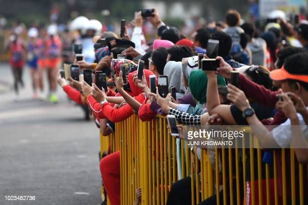 Spectators take photos as they watch athletes compete in the women's marathon athletics event during the 2018 Asian Games in Jakarta on August 26 2018