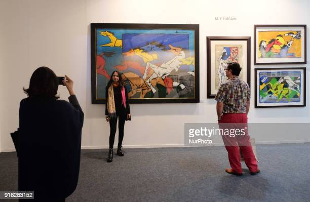 Spectators take photos in front of paintings by famous artist M. F. Husain at the India Art Fair 2018 held on the Okhla NSIC grounds in New Delhi on...