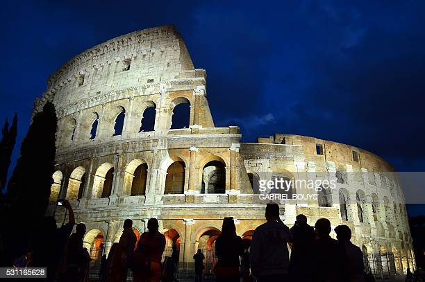 Spectators take photos of an illuminated Colosseum marking 150 years of diplomatic relations between Italy and Japan on May 12 2016 in downtown Rome...