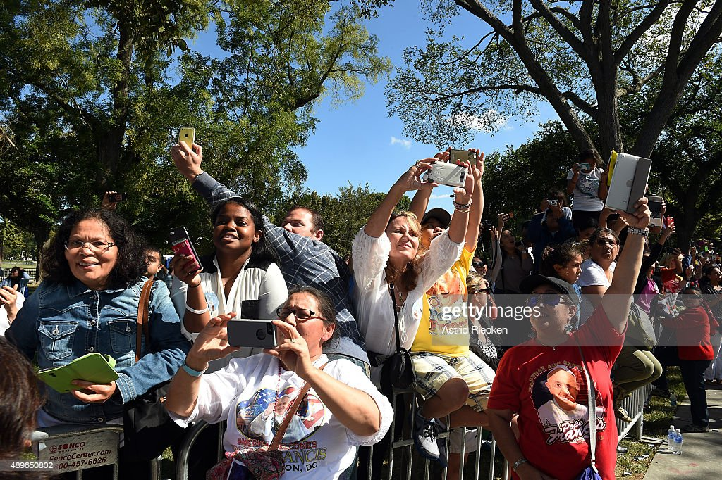 Spectators take photos of Pope Francis during a parade on the streets around the Ellipse, south of the White House, September 23, 2015 in Washington, DC. Thousands of people gathered near the Ellipse to catch a glimpse of Pope Francis after he addressed an audience of 15,000 invited guests on the South Lawn of the White House during an official arrival ceremony with President Barack Obama. The Pope began his first trip to the United States at the White House followed by a visit to St. Matthew's Cathedral, and will then hold a Mass on the grounds of the Basilica of the National Shrine of the Immaculate Conception.