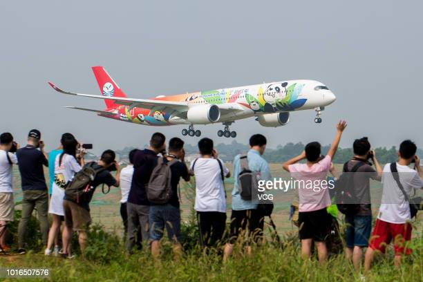 Spectators take photos of Sichuan Airlines' pandathemed Airbus A350900 upon its arrival at the Chengdu Shuangliu International Airport on August 9...