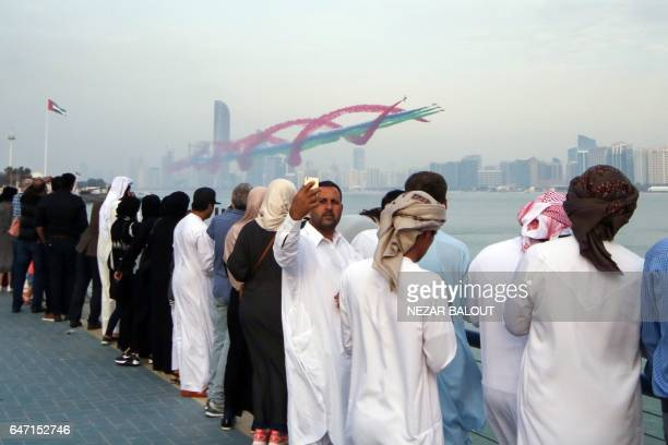 TOPSHOT Spectators take pictures of planes performing in an Emirati airshow as part of the 'Union Fortress Live Military Demonstration' at the Abu...