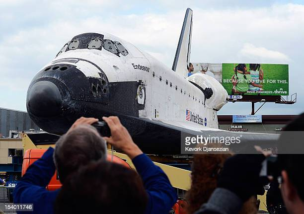 Spectators take pictures of the space shuttle Endeavour parked in a mall parking lot on October 12 2012 in Los Angeles California The space shuttle...