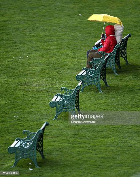 Spectators take shelter from the rain at Ascot racecourse on April 27 2016 in Ascot England