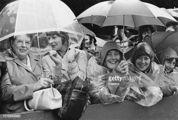 Spectators take shelter under umbrellas as rain stops play during the 1972 Wimbledon Championships at the All England Club in London, England, 9th...