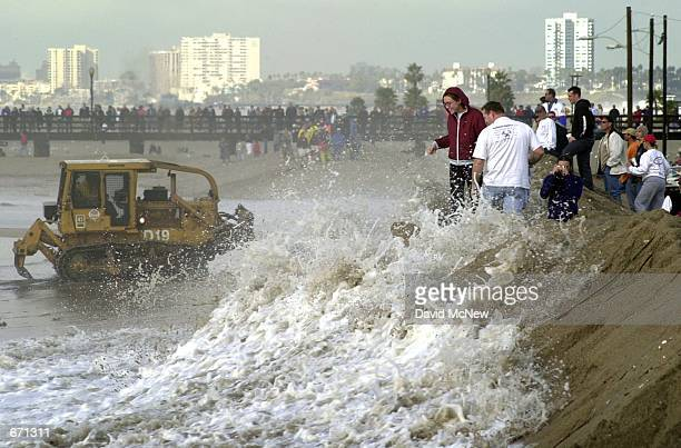Spectators temp fate by standing their ground as a wave rushes up the sand berm which is protecting coastal homes from flooding by the stormdriven...