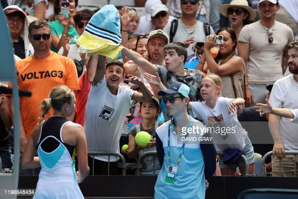 Spectators try to catch Estonia's Anett Kontaveit towel after her women's singles match against Poland's Iga Swiatek on day eight of the Australian...