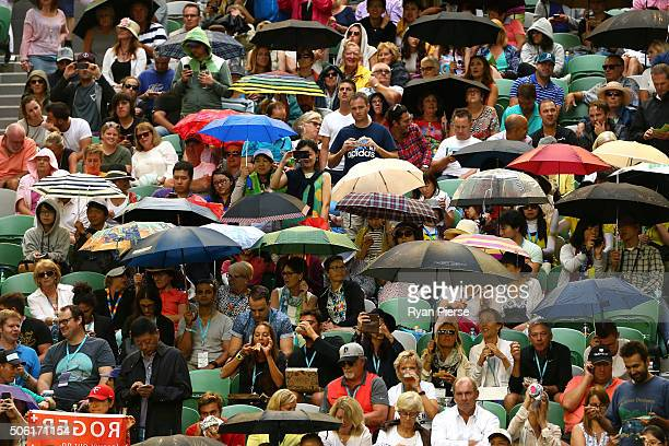 Spectators try to stay dry underneath their umbrellas during the rain delay at Rod Laver Arena during Roger Federer of Switzerland third round match...