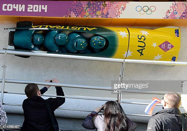 Spectators try to take a photo of the Australia 1 bobsled as it passes and competes in the third heat of the fourman bobsled event at the Sanki...