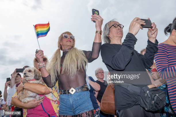 Spectators using mobile phones during the annual Brighton Pride parade on the 3rd August 2019 in Brighton in the United Kingdom