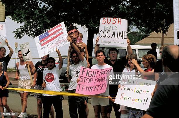 Spectators w signs incl Welcome Pres Reagan Bush deals Cocaine through contras antiIsraeli antiapartheid slogans during Reagan visit