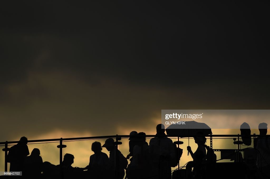 TOPSHOT - Spectators wait as rain stops play at the All England Tennis Club in Wimbledon, southwest London, on July 4, 2018, on the third day of the 2018 Wimbledon Championships tennis tournament. (Photo by Glyn KIRK / AFP) / RESTRICTED