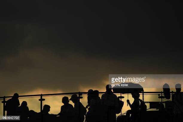 TOPSHOT Spectators wait as rain stops play at the All England Tennis Club in Wimbledon southwest London on July 4 on the third day of the 2018...