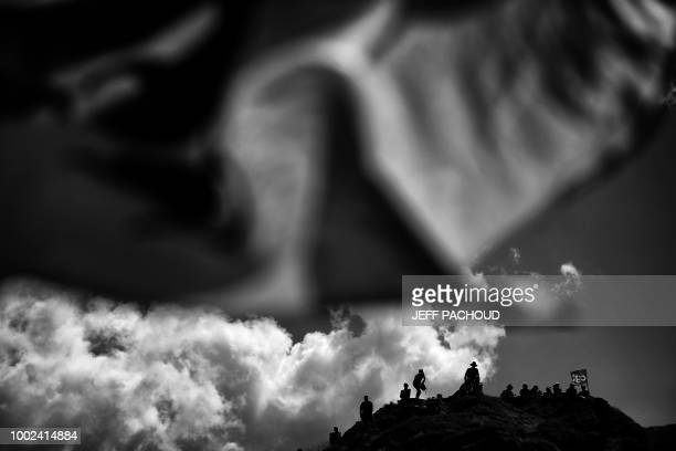Spectators wait atop a hill to watch riders during the twelfth stage of the 105th edition of the Tour de France cycling race between...