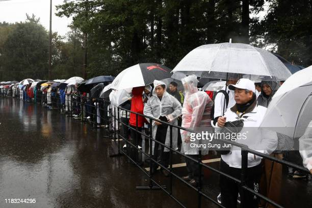 Spectators wait for shuttle buses in front of the gate after the second round of the Zozo Championship is postponed due to heavy rain at Accordia...