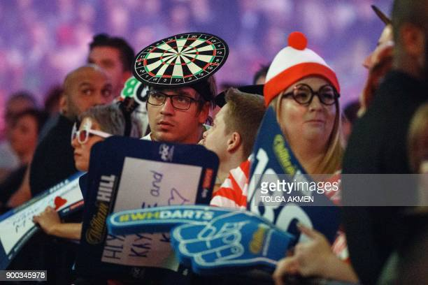 Spectators wait for the start of the PDC World Darts Championship 2018 final game between English professional darts player Phil Taylor and English...