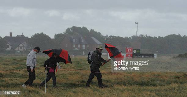 Spectators wait in bad weather for play to resume during the second round of the Women's British Open golf tournament at the Royal Liverpool Golf...
