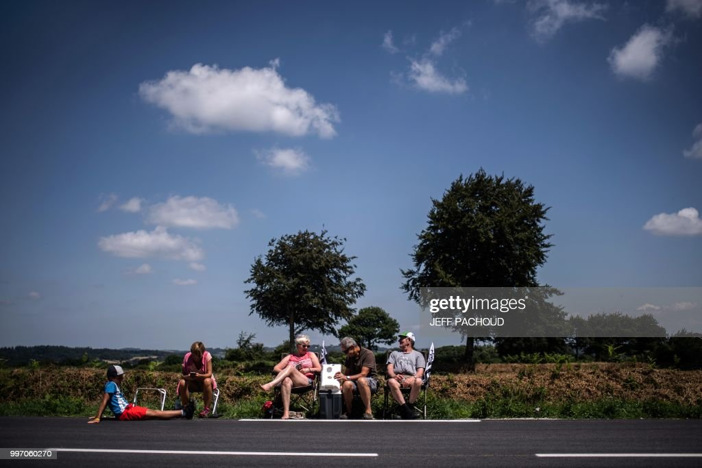TOPSHOT - Spectators wait in Mur-de-Bretagne by the finish line of the sixth stage of the 105th edition of the Tour de France cycling race between Brest and Mur-de-Bretagne Guerledan, western France, on July 12, 2018.