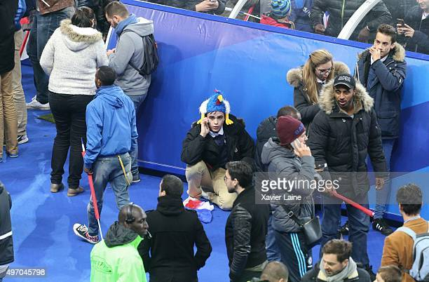 Spectators wait on the pitch of the during the International Friendly game between France and Germany at Stade de France on November 13 2015 in Paris...