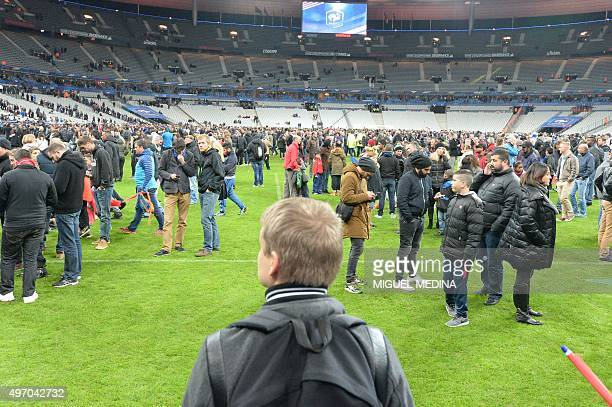 Spectators wait on the pitch of the Stade de France stadium in SeineSaintDenis Paris' suburb on November 13 2015 after a series of gun attacks...