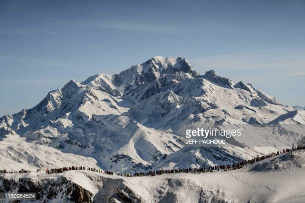 TOPSHOT Spectators wait skiers in front of the Mont Blanc during the fourth and last stage of the 34th edition of the skimountaineering race the...