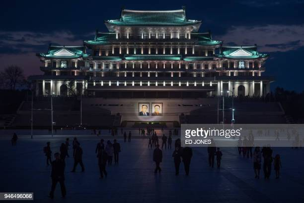 Spectators walk across Kim Il Sung square as they arrive to watch a fireworks display during celebrations marking the anniversary of the birth of...