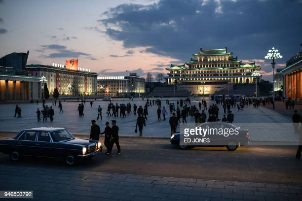 TOPSHOT Spectators walk across Kim Il Sung square as they arrive to watch a fireworks display during celebrations marking the anniversary of the...