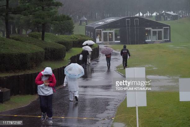 Spectators walk in the rain as the PGA ZOZO Championship golf tournament had been postphoned at the Narashino Country Club in Inzai Chiba prefecture...