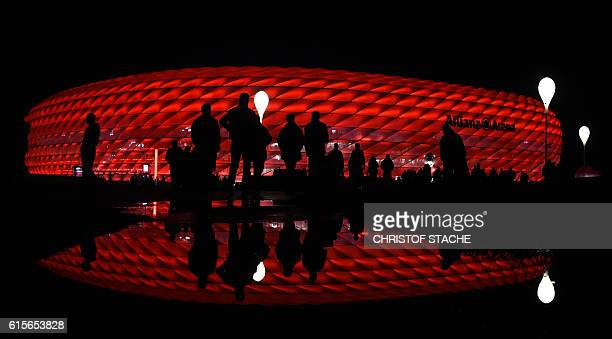 Spectators walk outside the stadium ahead the UEFA Champions League group D football match FC Bayern Munich vs PSV Eindhoven in Munich on October 19...
