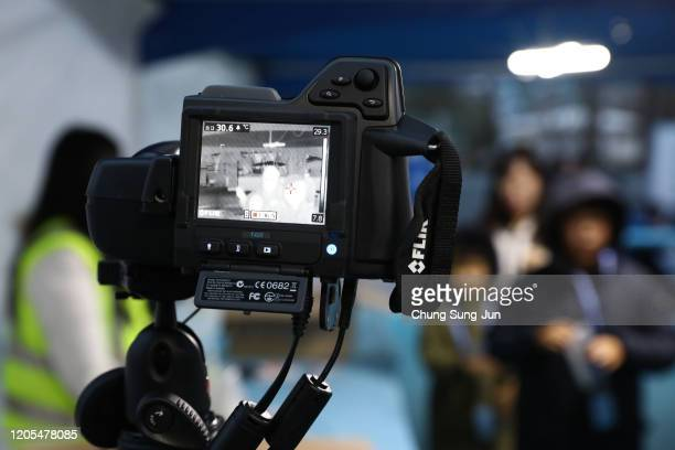Spectators walk past a thermal camera in light of the novel coronavirus ahead of the AFC Champions League Group F match between Ulsan Hyundai and FC...