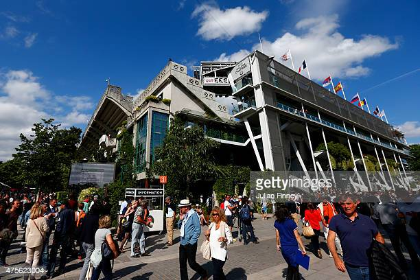 Spectators walk past Court Philippe Chatrier after a piece of metal was blown off in high winds during the men's singles quarterfinal match between...