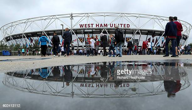 Spectators walk to the stadium before the Premier League match between West Ham United and Watford at the Olympic Stadium on September 10 2016 in...