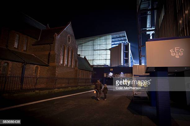 Spectators walking past St Luke's church towards Goodison Park Liverpool before the Premier League match between Everton and West Bromwich Albion The...