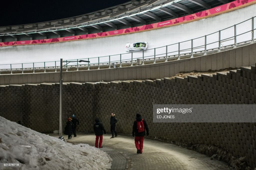 TOPSHOT - Spectators watch a bobsleigh pass during the women's bobsleigh heats during the Pyeongchang 2018 Winter Olympic Games at the Olympic Sliding Centre in Pyeongchang on February 20, 2018. / AFP PHOTO / Ed JONES