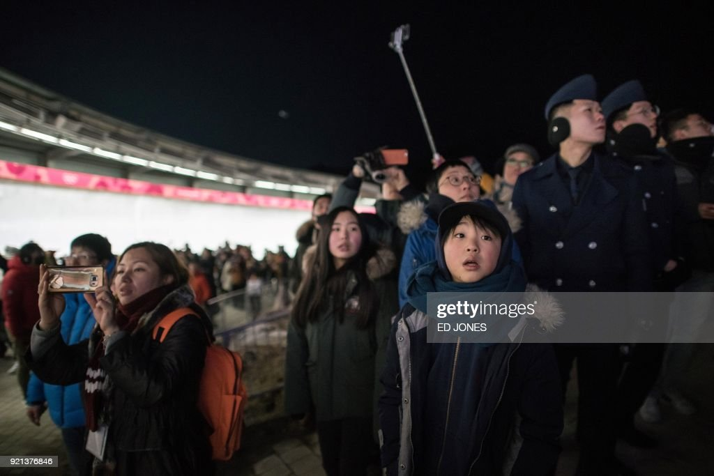 Spectators watch a bobsleigh pass during the women's bobsleigh heats during the Pyeongchang 2018 Winter Olympic Games at the Olympic Sliding Centre in Pyeongchang on February 20, 2018. / AFP PHOTO / Ed JONES