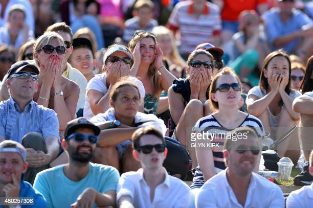 Spectators watch a giant screen showing the men's semifinal match between Switzerland's Roger Federer and Britain's Andy Murray from Murray Mound on...