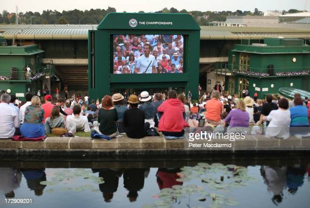 Spectators watch a giant TV screen showing Andy Murray of Great Britain's men's singles semi final match against Jerzy Janowicz of Poland on day...