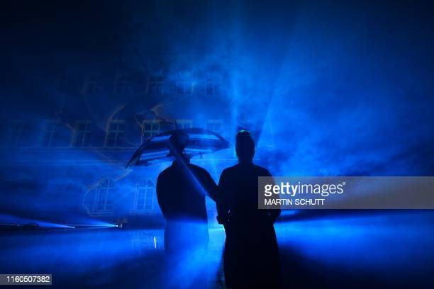 """Spectators watch a light installation that is part of the """"Genius Loci"""" illumination festival in Weimar, eastern Germany, on August 9, 2019. /..."""