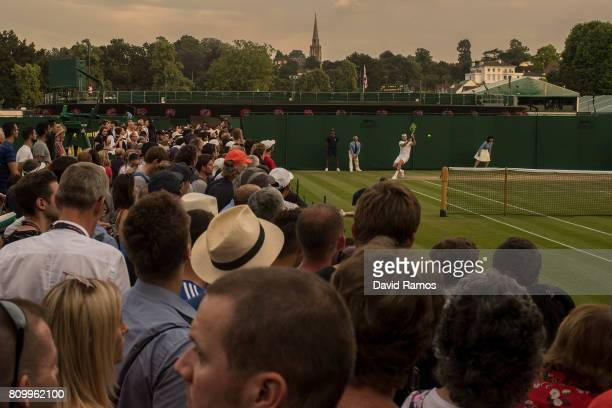 Spectators watch a match in the outside courts on day four of the Wimbledon Lawn Tennis Championships at the All England Lawn Tennis and Croquet Club...