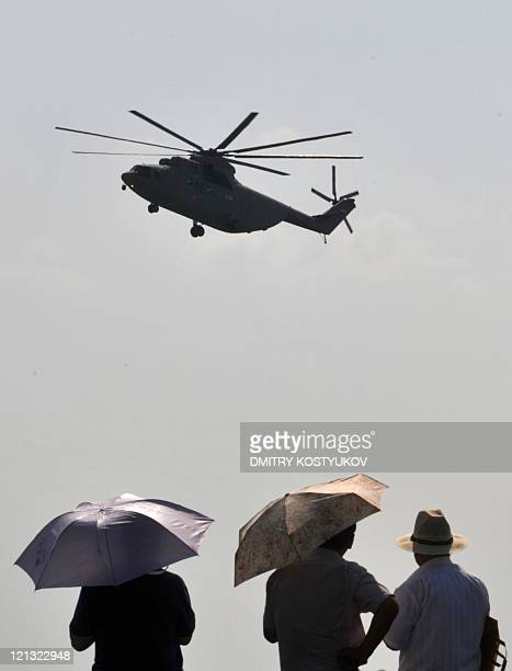 Spectators watch a Russian Mi-26 helicopter in flight during MAKS-2011, the International Aviation and Space Show, in Zhukovsky, outside Moscow, on...