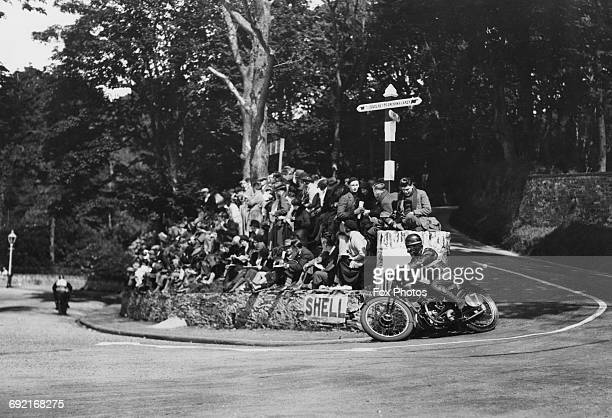 Spectators watch as a competitor rides around the Governor's Bridge hairpin during the Isle of Man Senior TT Tourist Trophy motorcycle race on 18...
