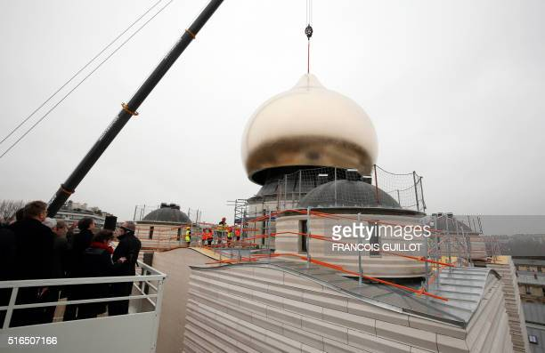 Spectators watch as a crane places a cupola on top of the future Russian orthodox cathedral SainteTrinite at Quai Branly central Paris on March 19...