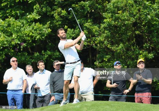 Spectators watch as actor Jamie Dornan plays a shot during the BMW PGA Championship Pro Am tournament at Wentworth on May 23 2018 in Virginia Water...