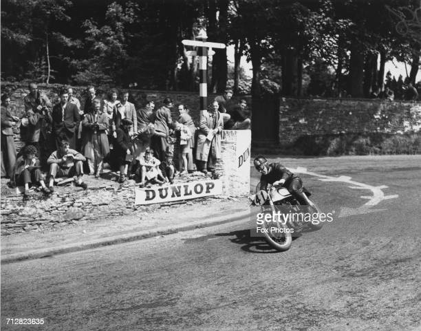 Spectators watch as Artie Bell of Great Britain rides the Norton 500cc motorcycle around Governor's Bridge hairpin during the Isle of Man Senior TT...